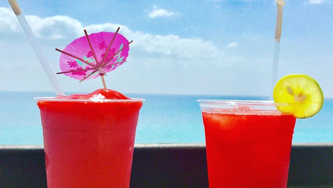 Red slushy cocktails by the ocean