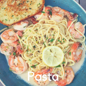 A plate of shrimp pasta with garlic bread