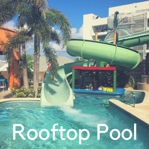 A slide from a rooftop pool into another pool