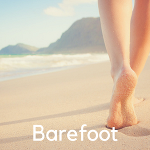 A woman walking barefoot on the beach