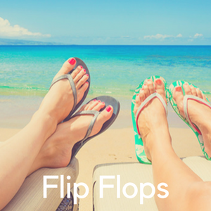 Two pairs of feet in flip flops on the beach