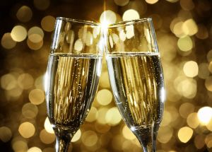 Two champagne glasses cheers-ing with a gold background.