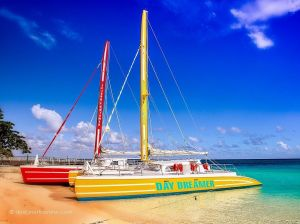 Two colorful sailboats are docked and waiting to take travellers on a Caribbean boat cruise