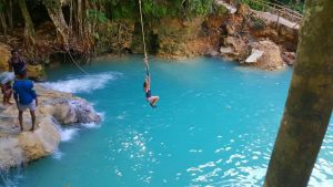 A woman swings from a rope and into a lagoon while on a Jamaican excursion adventure