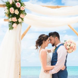 A couple embrace and celebrate their Jamaican wedding on the beach