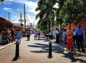 Pedestrians stroll down a cobblestone street while doing their Montego Bay shopping